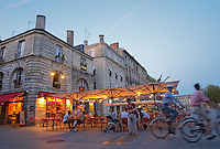 A cafe on the place pey berland in Bordeaux, outside seating terrasse lit by electric lights, cyclists passing by and a woman waiting, Place Pey Berland. city Bordeaux Gironde Aquitaine France