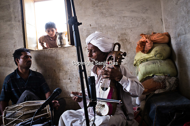 A young boy peeps in through the window while 66-year-old Manganiyar artist, Lakha Khan (right) plays the Sarangi with his son, Dane Khan accompanying him on the Dholak in their house in Raneri village of Jodhpur district in Rajasthan, India. Photo: Sanjit Das/Panos