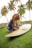 INDONESIA, Mentawai Islands, Kandui Surf Resort, girl waxing surfboard on lawn with palm trees in the background
