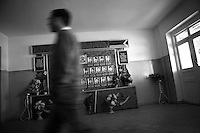 """Nagorny-Karabach, 16.05.2011, Shushi. Ein Mann geht im Eingangsbereich einer Schule an einer Galerie von gefallenen Kriegshelden vorbei. """"The Twentieth Spring"""" - ein Portrait der s¸dkaukasischen Stadt Schuschi, 20 Jahre nach der Eroberung der Stadt durch armenische K?mpfer 1992 im B¸gerkrieg um die Unabh?ngigkeit Nagorny-Karabachs (1991-1994). A man walks by a display of portraits of fallen Karabakh veterans in a schools entrance. """"The Twentieth Spring"""" - A portrait of Shushi, a south caucasian town 20 years after its """"Liberation"""" by armenian fighters during the civil war for independence of Nagorny-Karabakh (1991-1994). .Un homme marche devant des portraits de vétérans Karabakhs tombéslors de la guerre d'indépendance, dans l'entrée de l'école.""""Le Vingtieme Anniversaire"""" - Un portrait de Chouchi, une ville du Caucase du Sud 20 ans après sa «libération» par les combattants arméniens pendant la guerre civile pour l'indépendance du Haut-Karabakh (1991-1994)..© Timo Vogt/Est&Ost, NO MODEL RELEASE !!"""