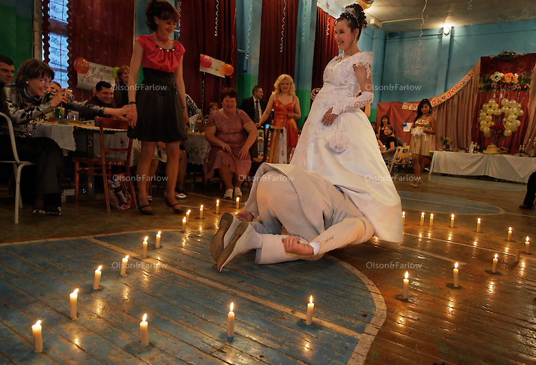 Groom Ivan Osipova does handless garter diving in candles of love.