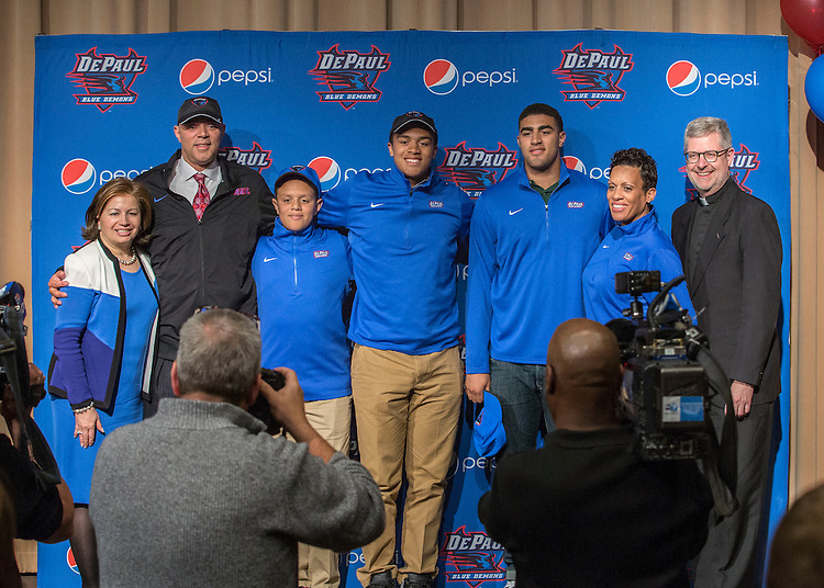 Athletics Director Jean Lenti Ponsetto, left, and the Rev. Dennis H. Holtschneider, C.M., president of DePaul University, right, join Dave Leitao and his family on stage after he was named the new head coach of the men's basketball program Monday, March 30, 2015. (DePaul University/Jamie Moncrief)