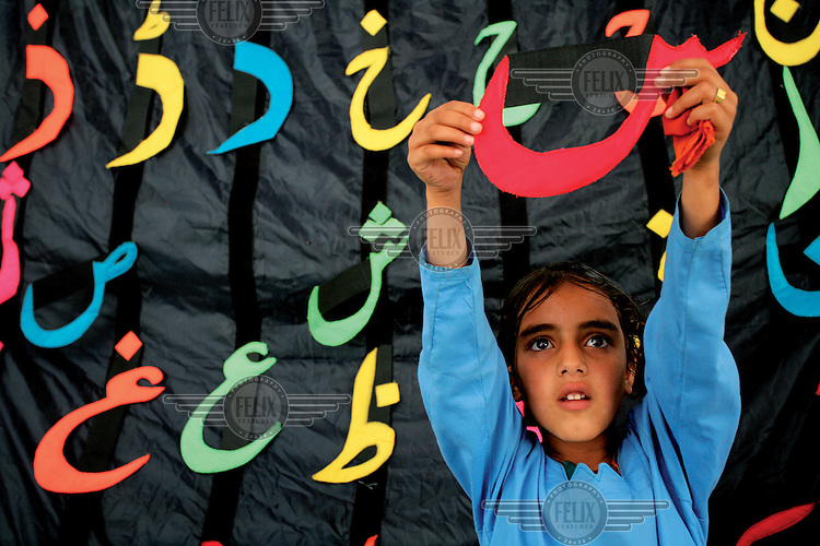 A girl in primary school holds up an Arabic character..