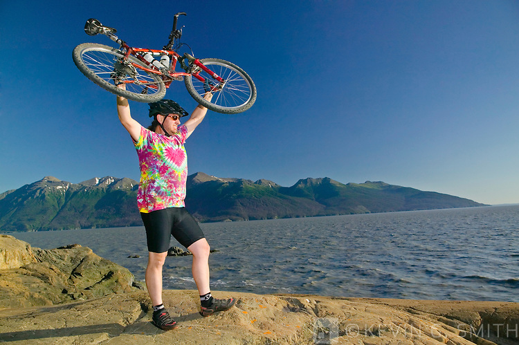Middle aged man, caucasian, standing on the shore holding his mountain bike above his head after completing his ride, Turnagain Arm, Summer, Kenai mountains in the background, Southcentral Alaska, USA. MR.