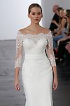 Model walks runway in an off-the-shoulder dropped waist sheath bridal gown with long sleeve lace bodice and chiffon sash, from the Dennis Basso for Kleinfeld 2018 Bridal Collection on October 5 2017, during New York Bridal Fashion Week.