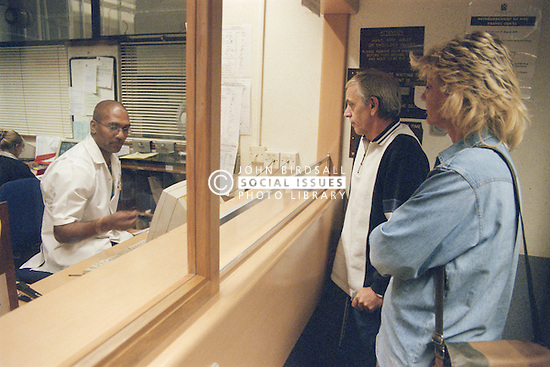 Man and woman giving medical receptionist their details in Accident and Emergency department of hospital,