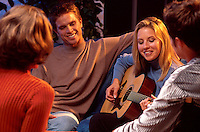 Smiling young couples socializing and listening to a female play the guitar.