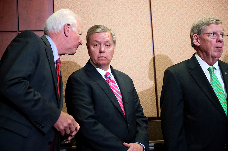 UNITED STATES - MAY 14: From left, Sens. John Cornyn, R-Texas, Lindsey Graham, R-S.C., and Johnny Isakson, R-Ga., attend a news conference in the Capitol Visitor Center to oppose the deactivation of the A-10 fighter aircraft, May 14, 2014. (Photo By Tom Williams/CQ Roll Call)
