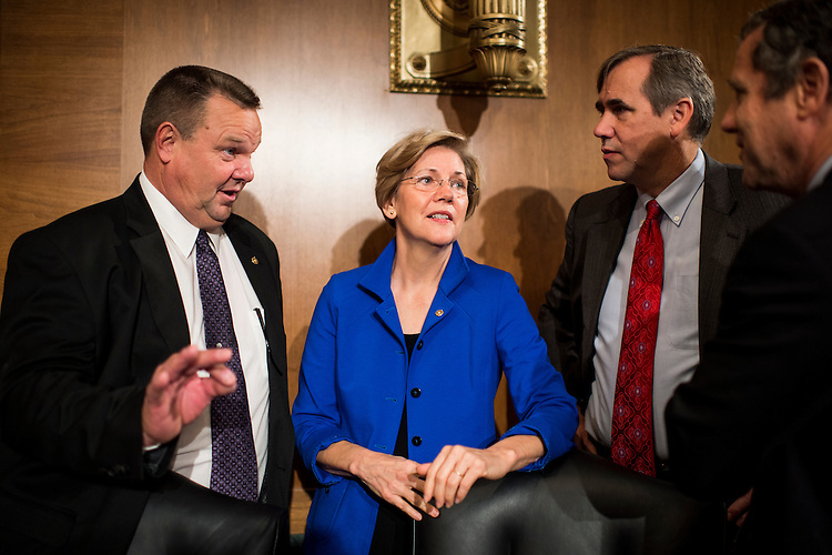 """UNITED STATES - OCTOBER 10: From left, Sen. Jon Tester, D-Mont., Sen. Elizabeth Warren, D-Mass., Sen. Jeff Merkley, D-Ore., and Sen. Sherrod Brown, D-Ohio, talk before the start of the Senate Banking, Housing and Urban Affairs Committee hearing on """"Impact of a Default on Financial Stability and Economic Growth"""" on Thursday, Oct. 10, 2013. (Photo By Bill Clark/CQ Roll Call)"""