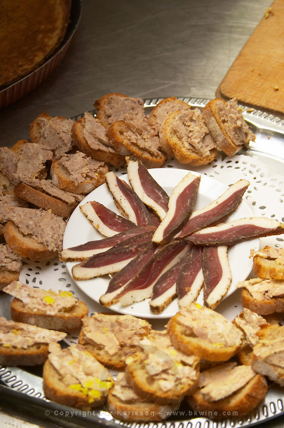 Duck appetizers: dried duck breast and small canapees pieces of bread with duck rillettes Ferme de Biorne duck and fowl farm Dordogne France