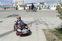 A young bit rides a toy car on the Tibetan Plateau, in western China.