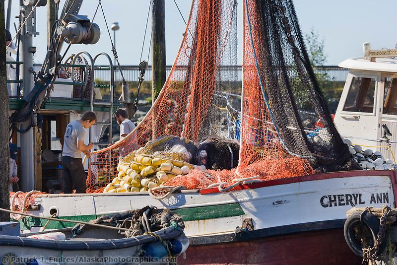 Fishermen mend net on the Cheyrl Ann, Thomas Basin harbor, Ketchikan, Alaska.