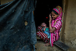 A woman carries an infant and sits on the entrance of her room at a camp for Rohingya people.