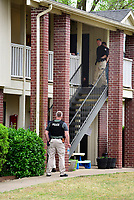 NWA Democrat Gazette/SPENCER TIREY Little Flock police officers and Benton County Sheriffs deputies talk outside an apartment in the Fairways at Lost Springs Apartments complex after two people were shot early Friday morning.
