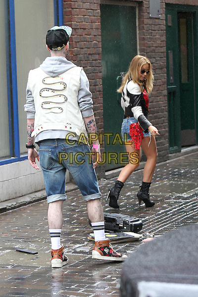 Kylie Minogue shoots a her new pop video in central London, England..April 19th, 2012.full length film filming black boots leather jacket white red heart print jacket denim jean cut offs shorts sunglasses shades  funny gesture drop dropping looking over shoulder.CAP/HIL.©John Hillcoat/Capital Pictures .