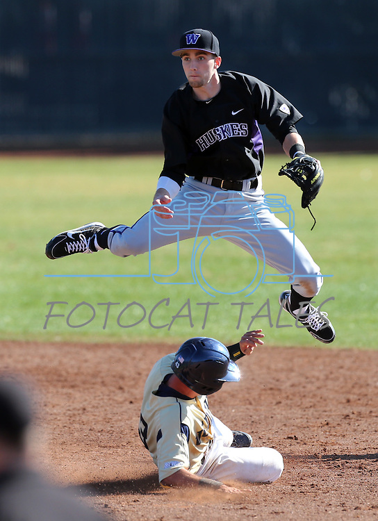 Huskies' Erik Forgione leaps over Aggies' John Williams in a college baseball game between the Washington Huskies and the UC Davis Aggies in Davis, Ca., on Sunday, Feb. 17, 2013. Davis won 7-5 to finish their season opening series 3-1. .Photo by Cathleen Allison
