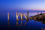 Salt encrusted pilings from a ruined dock reflect in the still twilit waters of the Salton Sea at Bombay Beach, California