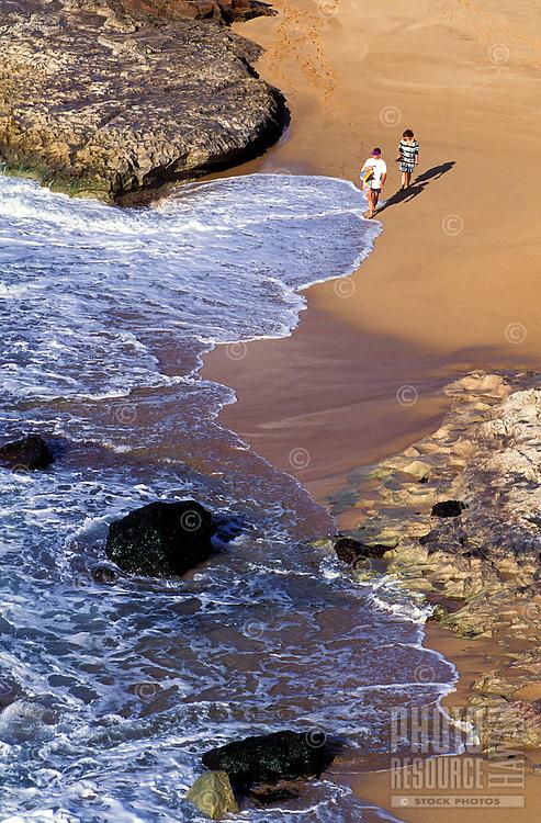 A couple walks along the sand at Kepuhi Beach on Molokai.