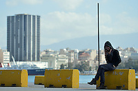 Pictured: A man speaks to his mobile phone having just arrived to Piraeus port, Greece Sunday 28 February 2016<br /> Re: Hundreds of migrants have arrived from the Greek islands to Piraeus Port, Greece