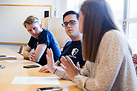 """Sam Carson (left), 28, a Master in Public Policy graduate student at Harvard, listens to Molly Osborne (foreground), 27, during the Resistance School logistics group volunteer meeting before a session of Resistance School in the Taubman Building of Harvard University's John F. Kennedy School of Government, on Thurs., April 27, 2017. The goal of the meeting was to plan how to direct attendees from the registration location to the lecture location. Resistance School was started by progressive graduate students at Harvard after the Nov. 8, 2016, election of President Donald Trump. Resistance School describes itself as a """"practical training program that will sharpen the tools [needed] to fight back at the federal, state, and local levels."""" Resistance School puts on live lectures by leading progressives that are streamed and archived online alongside other information on the Resistance School website. During the lectures, teams of volunteers engage with followers on social media, including Facebook and twitter, sharing soundbytes, quotations, and supplementary materials as the lectures happen."""