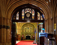 A carved wooden partition, with stained glass windows and folding doors, marks the entrance to another ante-room, complete with heraldic fireplace and leather armchairs