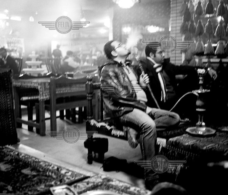 A man smokes a shisha (sheesha, narghile, hookah) in a coffeshop.