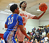 Deven Williams #5 of Half Hollow Hills West, right, draws a shooting foul during a varsity boys' basketball game against Archbishop Molloy at Long Island Lutheran High School on Sunday, Jan. 3, 2016. Archbishop Molloy defeated Hills West by a score of 70-56.