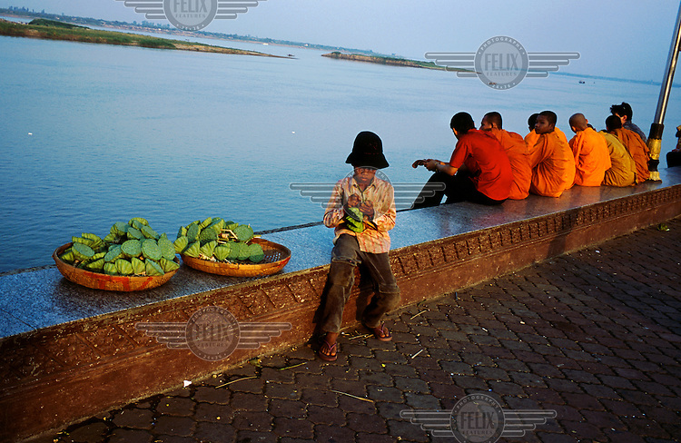 Young boy selling lotus heads on the city's waterfront at Sisowath Quay next to the Tonle Sap River.