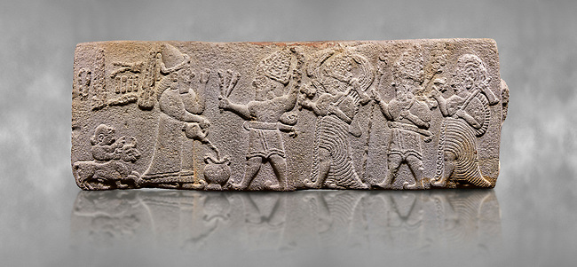 Aslantepe Hittite relief sculpted orthostat stone panel. Limestone, Aslantepe, Malatya, 1200-700 B.C. . Anatolian Civilisations Museum, Ankara, Turkey<br /> <br /> Scene of the king's offering drink and sacrifice to the gods. King pours from the pitcher to the vessel (libation); behind the king is a servant bringing a sacrifice. Storm God across the king holds Teshup, a triple lightning bundle - sickle, and a spear-mace set in the other orthostat; the goddess Ishtar holds weapon in both. All six figures have shoes with the curled ends. <br /> <br /> Against a grey art background.