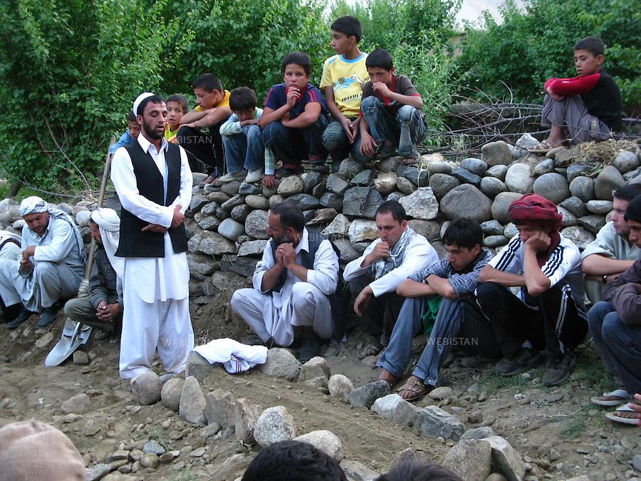 AFGHANISTAN - VALLEE DU PANJSHIR - MALASPEH - 13 aout 2009 : enterrement de Tahmineh, la niece du cameraman et ami de Massoud, Youssef Jan Nessar, morte noyee dans la riviere. Un membre du clerge recite une priere. ..AFGHANISTAN - PANJSHIR VALLEY - MALASPEH - August 13th, 2009 : A clergyman recites a prayer at the burial of Tahmineh.  The 8-year old niece of Youssef Jan Nessar, a cameraman and friend of Massoud's, died by drowning in the river.