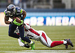 Seattle Seahawks  wide receiver Richardo Lockette (83) is wrapped up by Arizona Cardinals cornerback Patrick Peterson (21) after catching a pass from quarterback Russell Wilson at CenturyLink Field in Seattle, Washington on December 22, 2013.   The Cardinals beat the Seahawks 17-10.  ©2013. Jim Bryant Photo. ALL RIGHTS RESERVED.