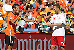 14 JUN 2010: Giovanni van Bronckhorst (NED) (left) and Dennis Rommedahl (DEN) (19) share a drink during and injury stoppage. The Netherlands National Team defeated the Denmark National Team 2-0 at Soccer City Stadium in Johannesburg, South Africa in a 2010 FIFA World Cup Group E match.
