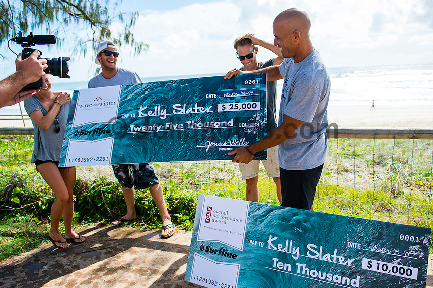 Tugun, Queensland Australia. (Friday March 21, 2014) –  Kelly Slater (USA) was presented with two checks this morning for Surfline's 2013 - 2014 Wave of the Winter and 2013 - 2014 US$10,000 Cliff Bar Overall Performance Award of the Winter. Sebastien Zietz (HAW) and Tommy Whitaker (AUS) surprised Kelly by jumping out from behind parked cars spraying him with soda water and presenting the US$25,000 Oakley Wave of the Winter check. Photo: joliphotos.com
