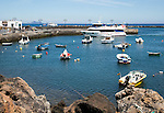 Harbour and ferry boat in the fishing village of Orzola, Lanzarote, Canary Islands, Spain
