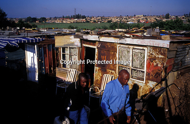 ditown00344 Township. Poverty,squatters,informal settlement,housing, shacks,.Unidentified men walks by Chris Hani, one of the poorest areas in Soweto, SA. His wife and child is going to fetch water in a nearby tap.  .©Per-Anders Pettersson/iAfrika Photos