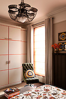 A master bedroom embraces strong colours as an accent. Orange features in the joinery of the cupboards and  and is complimented with a bed cover made from fabric. But most prominently orange sheers cover the floor to ceiling windows and flood the room in a warm inviting light.