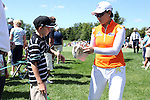 Se Ri Pak (right) signs some autographs before walking to the 6th tee at the 5th Annual Notah Begay III Foundation Challenge at Atunyote Golf Club in Vernon, New York on August 29, 2012