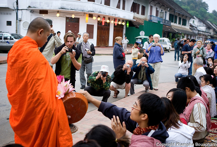 Tourist snap pictures of a buddhist monk as he make his morning alms round in Luang Prabang, Laos on Novemeber 6, 2009.   (Photo by Khampha Bouaphanh)