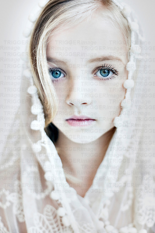 Close up of young girls face with blonde hair and blue eyes covering head with white lace veil looking at camera