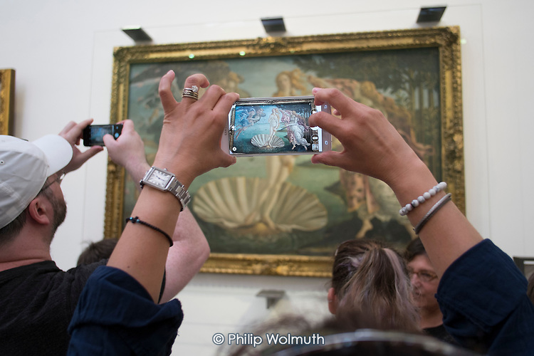 Tourists take smartphone photos of Botticelli's Birth of Venus in the Uffizi gallery, Florence, Italy.