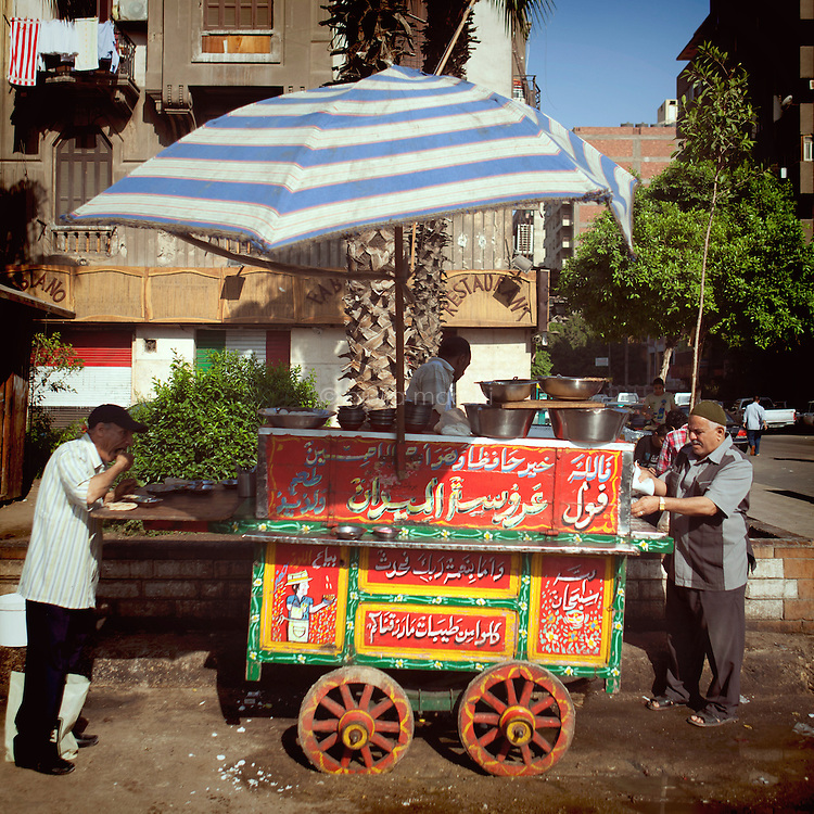 Egypt / Cairo / 21.5.2013 / Street scene in Cairo: at a 'ful' cart parked in Mounira, popular quarter of the city, people eat breakfast in the early morning. Ful is a typical food in Egypt, made of dried broad beans cooked in a metal jar over a low heat for hours, until the beans turn to a mush.