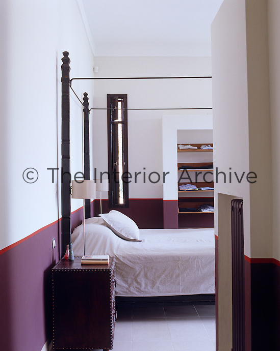 An otherwise simple bedroom has been given a sophisticated decorative twist with the introduction of a bold panel of colour around the wall