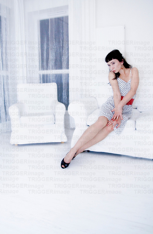 A young woman dressed in white pin up dress  with black dots and red belt sitting in a white room having hands on her knees