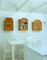A trio of old wooden Finnish cabinets creates an interesting wall display in this contemporary take on a country kitchen