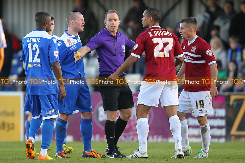 Harry Baker of Bishop's Stortford and Mathias Kouo-Doumbe of Northampton Town are held apart by referee Stepehn Martin - Bishop's Stortford vs Northampton Town - FA Challenge Cup 1st Round Proper Round Football at the Profit UK Stadium, Bishop's Stortford - 10/11/13 - MANDATORY CREDIT: Gavin Ellis/TGSPHOTO - Self billing applies where appropriate - 0845 094 6026 - contact@tgsphoto.co.uk - NO UNPAID USE