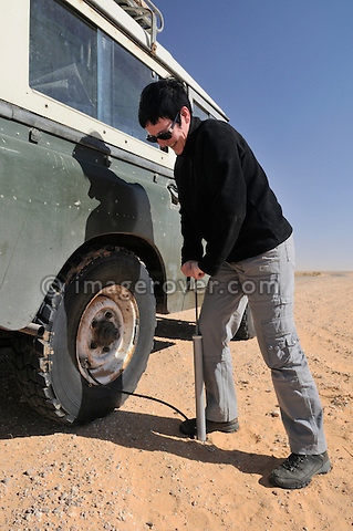 Africa, Tunisia, nr. Ksar Rhilane. Desert traveller Kerstin inflating a tyre with a hand compressor on a historic 1962 Land Rover. --- No releases available, but releases may not be needed for certain uses. Automotive trademarks are the property of the trademark holder, authorization may be needed for some uses.  --- Info: Image belongs to a series of photographs taken on a journey to southern Tunisia in North Africa in October 2010. The trip was undertaken by 10 people driving 5 historic Series Land Rover vehicles from the 1960's and 1970's. Most of the journey's time was spent in the Sahara desert, especially in the area around Douz, Tembaine, Ksar Ghilane on the eastern edge of the Grand Erg Oriental.