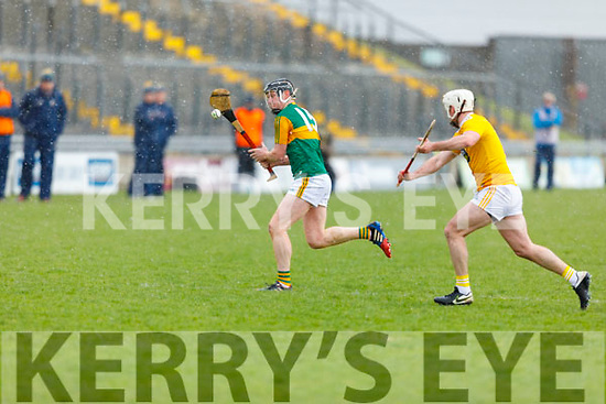 Brandon Barrett attempts a shot as Paddy Burke of Antrim bears down on him, in the NHL Div 2A hurling game in Austin Stack Park on Sunday
