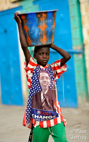 Wearing a shirt with an image of US President Barack Obama, a boy carries water in a bucket on his head in Timbuktu, the northern Mali city captured by Islamist forces in 2012 and liberated by French and Malian soldiers in 2013.