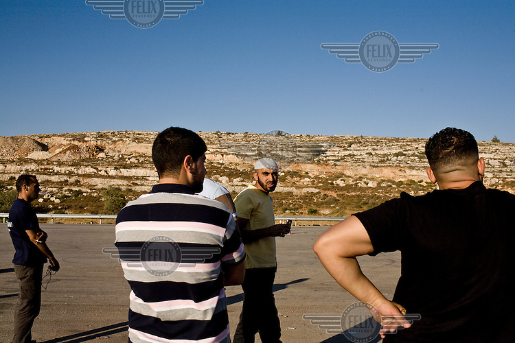 The boyfriends of the Speed Sisters and male Ramallah Racing Team members practice every Thursday at an abandoned piece of land outside Ramallah. The practice session is very close to an IDF checkpoint. Weekly permission must be granted for the West Bank racers to train there.