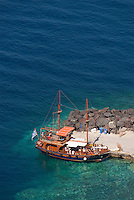 A schooner takes tourists on a tour of the Aegean Sea from the base of Oia town on the Greek island of Santorini.